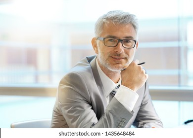Portrait of corporate businessman smiling at camera in office