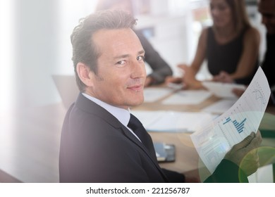 Portrait of corporate man sitting at meeting table