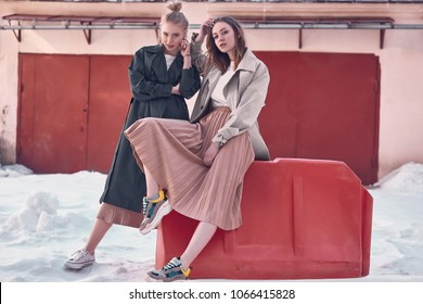 Portrait of a couple beautiful hipster girls wearing long fashion coats and dresses on the street