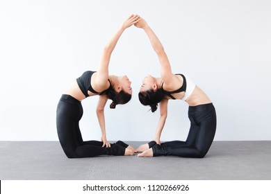 Portrait of couple beautiful young women wearing sportswear practicing yoga in studio,natural light.Concept : Partner yoga poses for beginner.Variation of the Camel Pose.