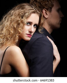 portrait of couple - blonde girl embraces man from behind. man's face in dark