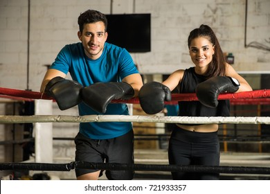 Portrait of a couple of boxers having a good time during training in a boxing gym and smiling