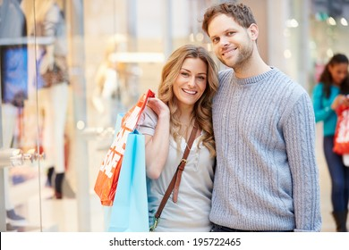 Portrait Of Couple Carrying Bags In Shopping Mall