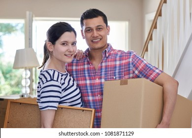 Portrait Of Couple Carrying Boxes Into New Home On Moving Day