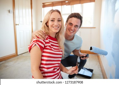 Portrait Of Couple Decorating Room In New Home Painting Wall Together