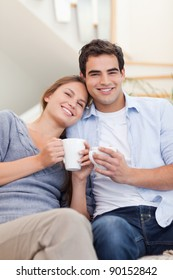 Portrait of a couple drinking coffee in their living room