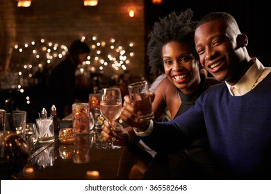 Portrait Of Couple Enjoying Night Out At Cocktail Bar