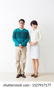 Portrait of couple in front of white wall