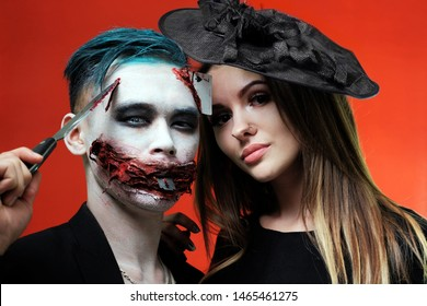 Portrait of a couple in halloween makeup style. The guy with the knife in the image of the joker and a beautiful girl in a hat like a witch. Bloody mouth with a razor blade and a seven-peak playing