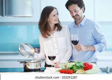 Portrait of a couple having a glass of red wine while cooking dinner