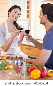 Portrait of a couple having a glass of red wine while cooking in their kitchen