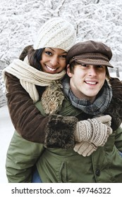 Portrait of couple having piggyback ride outdoors in winter