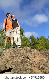 Portrait of a couple of hikers standing on a rock