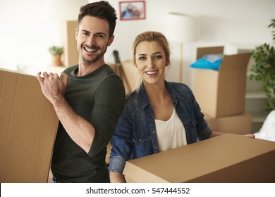 Portrait of couple holding cardboard boxes