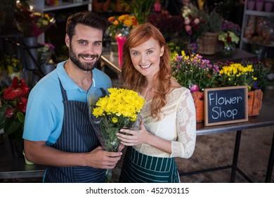 Portrait of couple holding flower bouquet in the flower shop