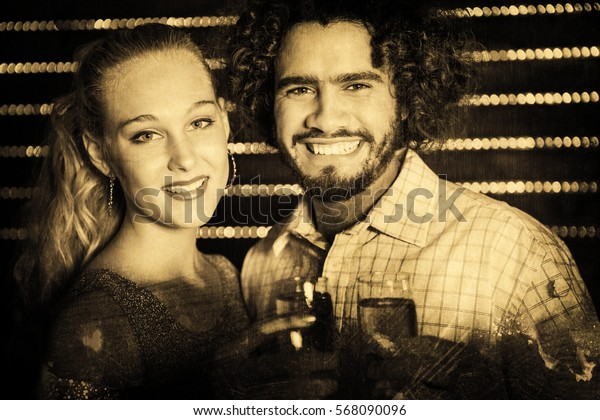 Portrait of couple holding glass of champagne in bar against grey background