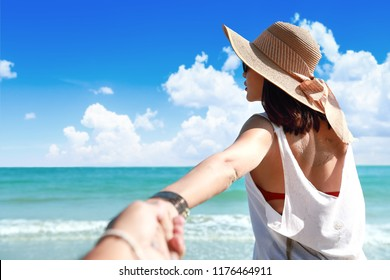 portrait of a couple holding hand on the beach with nice blue sky (this image for holiday vacation concept)