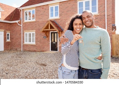 Portrait Of Couple Holding Keys Standing Outside New Home On Moving Day