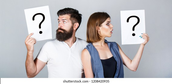 Portrait of couple holding paper question mark. Couple thinking about something. Confused couples with question marks. Conflict between two people. Pensive man and a thoughtful woman, conflict.