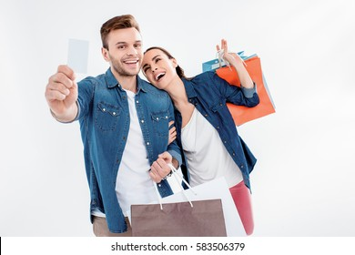portrait of couple holding shopping bags and credit card isolated on white