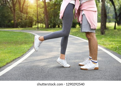 portrait of a couple legs wearing sport suit girlfriend kissing boyfriend (holiday vacation or valentine concept)