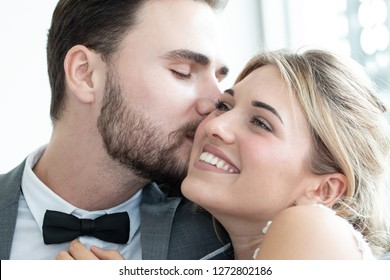 Portrait of Couple love or groom and bride try to fitting suit or dress in wedding studio with hug or kiss as romantic concept