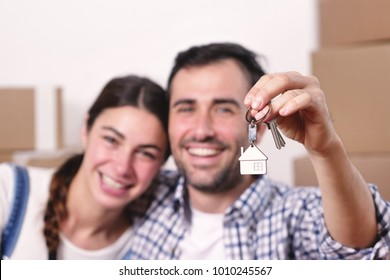 Portrait of a couple in love and they just bought a house and are moving. The bride and groom smile and hold the keys of the new house in their hands. Concept of: future, family