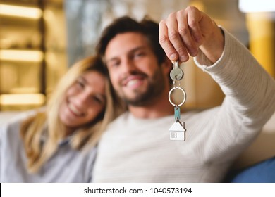 Portrait of a couple in love they just bought a house and are moving. The bride and groom smile and hold the keys of the new house in their hands. Concept of: future, family.