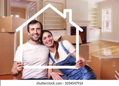 Portrait of a couple in love who have just bought a house and is moving. The bride and groom smile and hold and hold the outline of a house the in their hands. Concept of: home, family, ecology