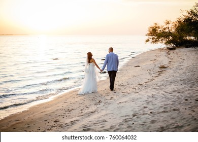 Portrait of Couple of lovers newlyweds on the seafront. Brunette bride in wedding dress with a beautiful hairstyle, veil and makeup and her husband