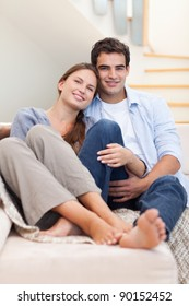 Portrait of a couple lying on a sofa while looking at the camera