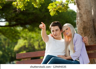 Portrait of couple on bench looking at something.