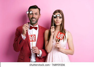 Portrait of couple with photo booth partying