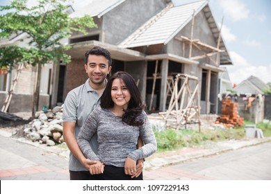portrait of couple proudly standing in front of their unfinished house