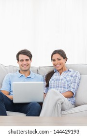 Portrait of a couple relaxing with a laptop sat on a couch