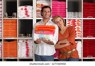 Portrait couple shopping for homeware choosing towels in store in front of colorful goods arranged on shelves and smiling at camera