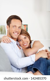 Portrait of couple sitting on couch and cuddling at home