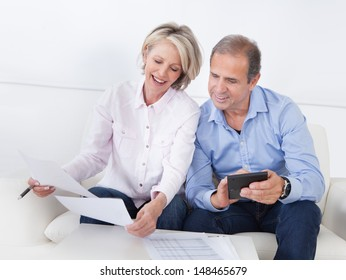 Portrait Of A Couple Sitting On Couch Enjoying Success
