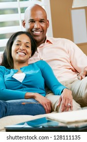 Portrait Of Couple Sitting On Sofa Together