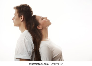Portrait of couple standing back to back. Pair of lovers who can not be together because of their families. They inhale every moment like it is their last one. Boy and girl feel like yin and yang