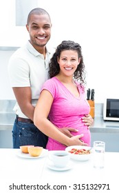 Portrait of couple standing in kitchen at home