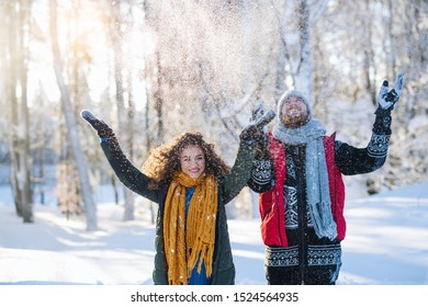 Portrait of couple standing outdoors in snow in winter forest, throwing snow.