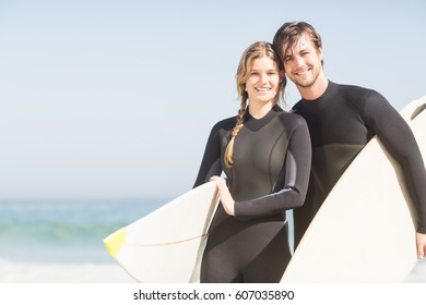 Portrait of couple with surfboard standing on the beach on a sunny day