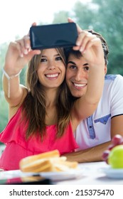 Portrait of couple taking photo of themselves with smart phone on romantic picnic.