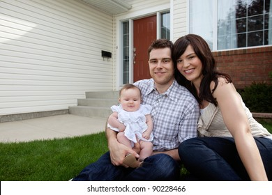 Portrait of couple with their adorable daughter sitting in front of house