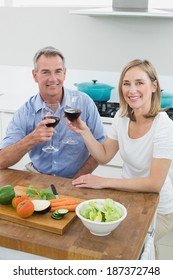 Portrait of a couple toasting wine glasses in the kitchen at home
