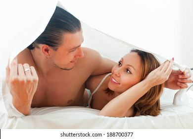 Portrait of  couple  together under sheet on bed