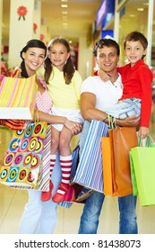 Portrait of couple with two children and shopping bags looking at camera and smiling
