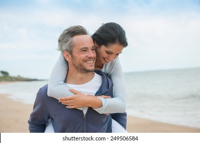 Portrait of a couple walking in the sand at the beach in casual clothes