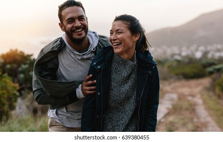 Portrait of couple walking through pathway on mountain. Man and woman enjoying vacation in countryside. Young people hiking in nature.